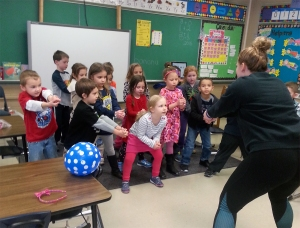 OFHS senior volleyball player Jordan Jaeckin teaches more than basic volleyball moves to Angela McNeeley 's kindergarten class as part of an exercise experience during the ECC's Wellness Week.